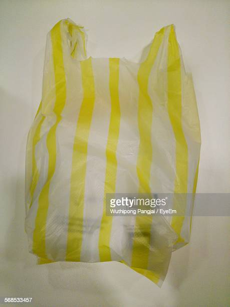 High Angle View Of Yellow Striped Polythene Bag Against Cream Background