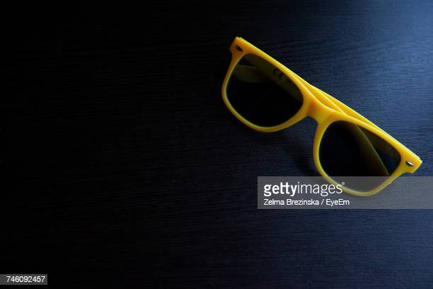 high angle view of yellow sunglasses on wooden table - brezinska stock pictures, royalty-free photos & images