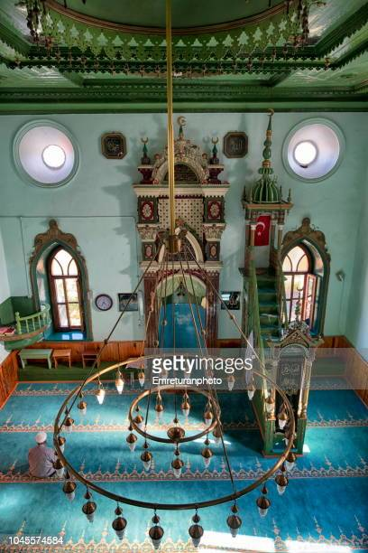 high angle view of yesilyurt village mosque interior with man praying,ayvacik,aegean turkey. - emreturanphoto stock pictures, royalty-free photos & images