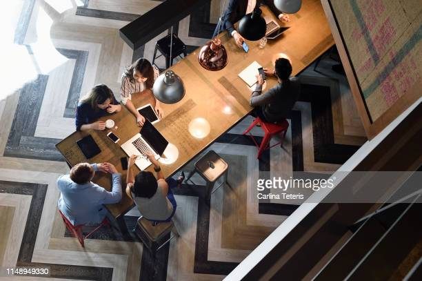 high angle view of young business executives working together - new business stock pictures, royalty-free photos & images