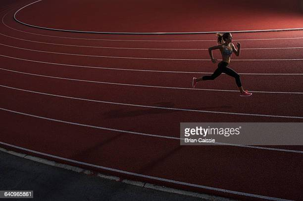 high angle view of young female athlete running on race track - training course stockfoto's en -beelden