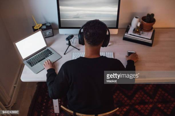 High angle view of young freelance worker using laptop and computer at desk