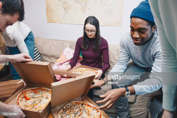 High angle view of young friends opening pizza boxes in dorm room