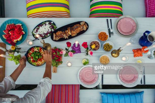 High angle view of young man arranging food on picnic table