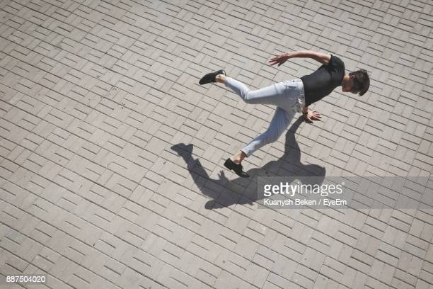high angle view of young man doing handstand on street - handstand stock pictures, royalty-free photos & images