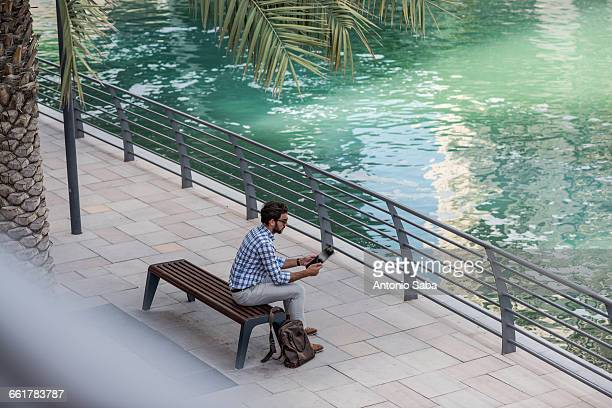 High angle view of young man sitting at waterfront using digital tablet, Dubai, United Arab Emirates