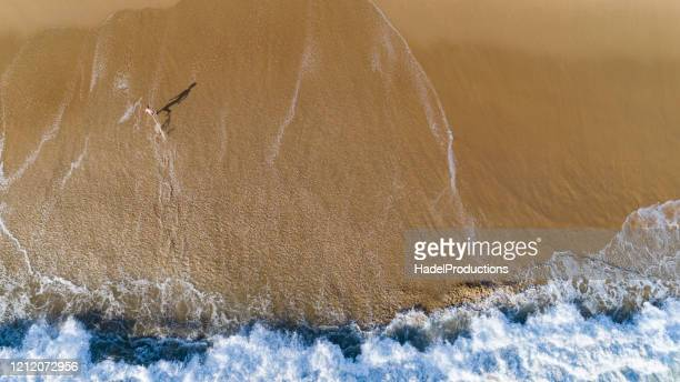 high angle view of young man standing on the beach - newport beach california stock pictures, royalty-free photos & images