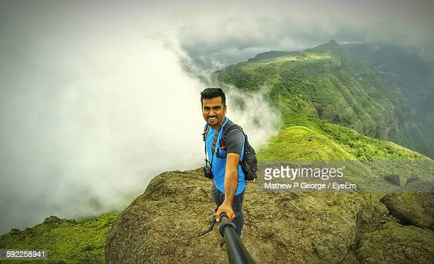 High Angle View Of Young Man Taking Selfie On Mountain Against Clouds