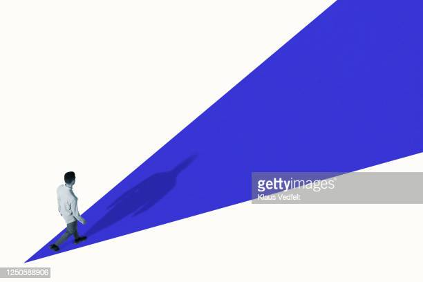 high angle view of young man walking on blue ramp - vision stock-fotos und bilder