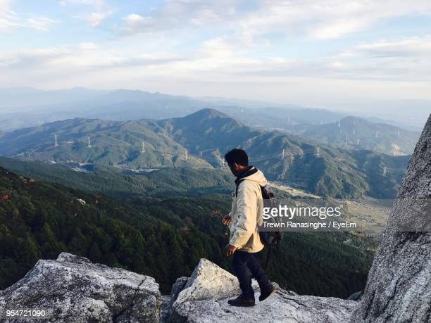 high angle view of young man walking on mountain against sky - fukuoka city stock pictures, royalty-free photos & images