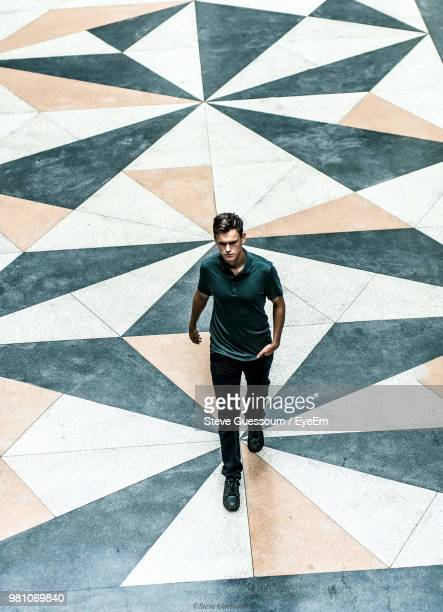 high angle view of young man walking on street - steve guessoum stockfoto's en -beelden