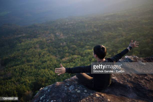 High Angle View Of Young Man With Arms Outstretched Sitting On Rock
