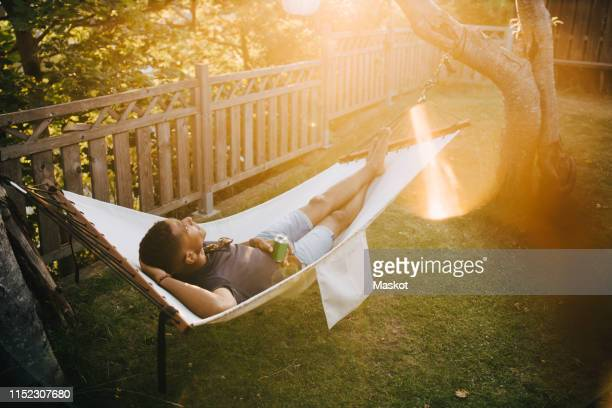 high angle view of young man with drink lying on hammock in back yard - hammock stock pictures, royalty-free photos & images