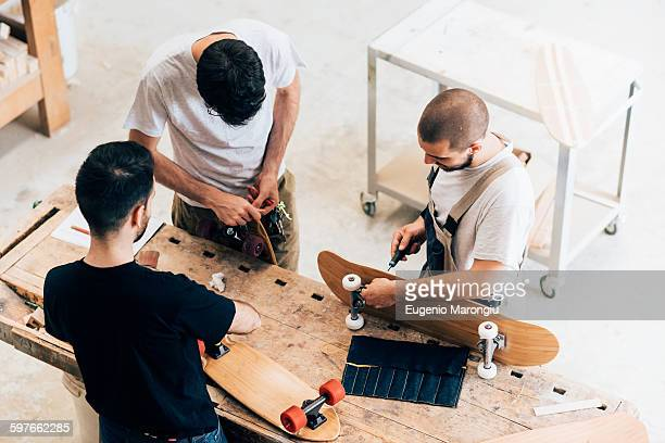 High angle view of young men standing around workbench attaching wheels to skateboards