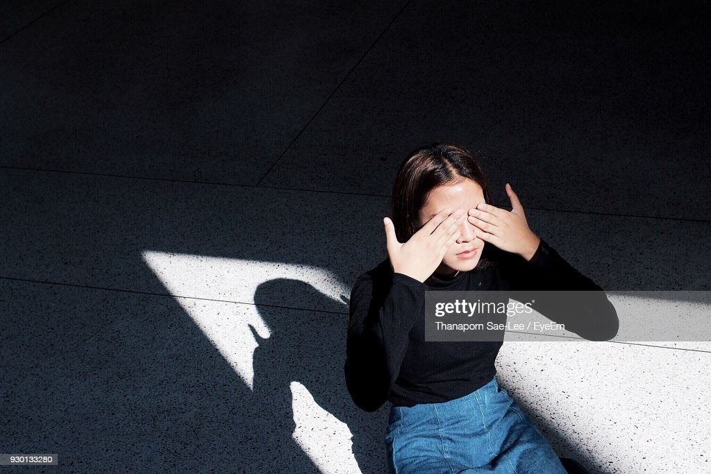 High Angle View Of Young Woman Covering Eyes With Hands While Sitting Outdoors : Stock Photo