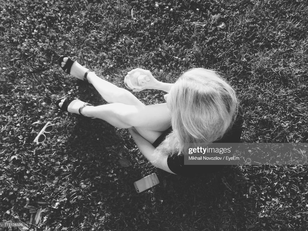 High Angle View Of Young Woman Holding Bottle While Sitting On Grassy Field : Photo
