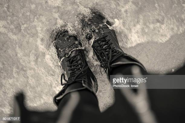 high angle view of young woman in laced boots in sea - bottines photos et images de collection