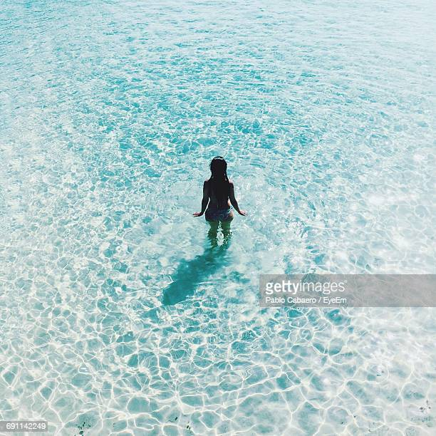 High Angle View Of Young Woman In Sea On Sunny Day