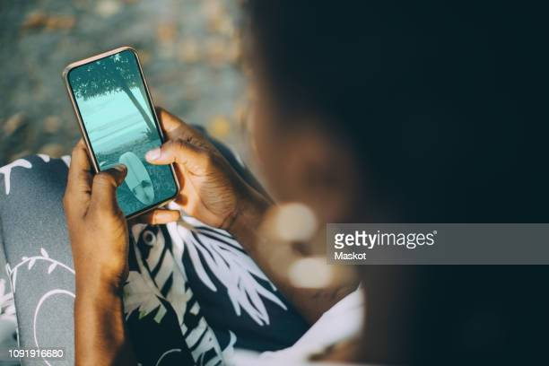 high angle view of young woman looking at beach photograph on smart phone - iphone screen stock pictures, royalty-free photos & images