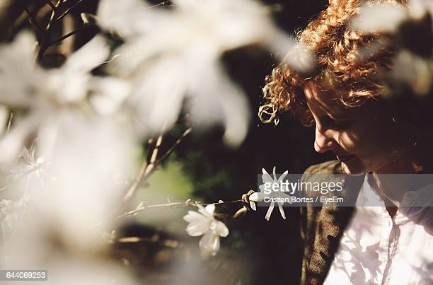 high angle view of young woman looking at white flower - bortes cristian stock photos and pictures