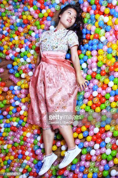 high angle view of young woman looking away while lying on colorful balls at home - coreia do sul - fotografias e filmes do acervo