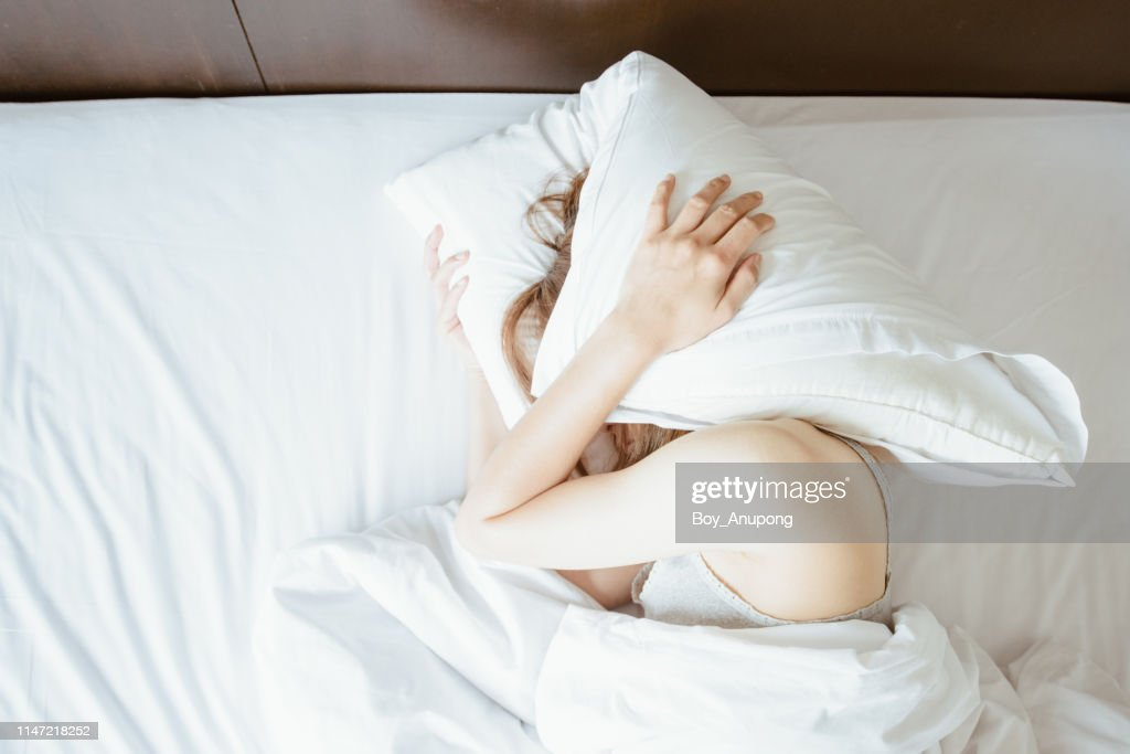 High angle view of young woman lying on bed and she hate to waking up in the early morning. : Stockfoto