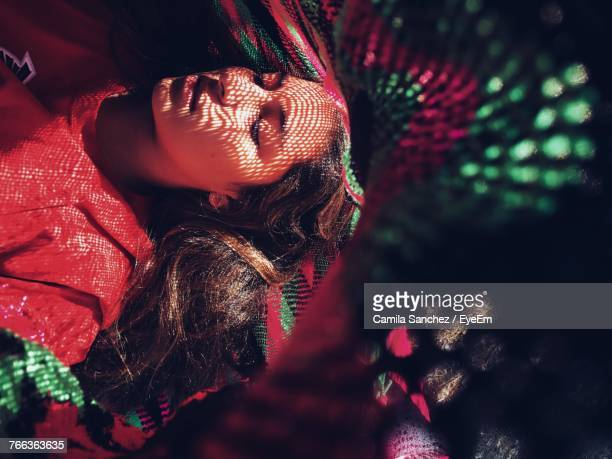 High Angle View Of Young Woman Lying On Hammock