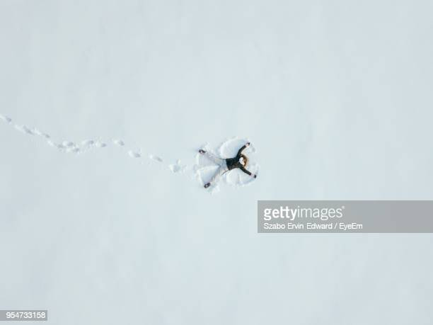 high angle view of young woman making snow angel - escapism stock photos and pictures