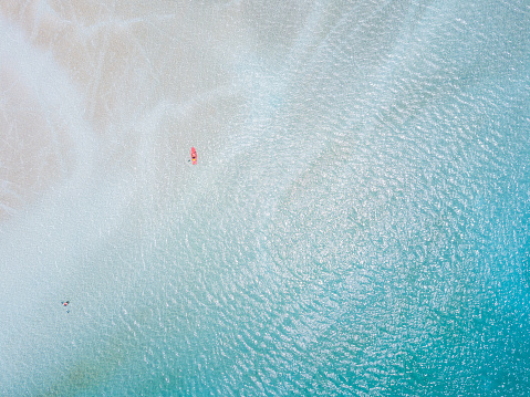 High angle view of young woman paddling in a canoe in the turquoise water. - gettyimageskorea