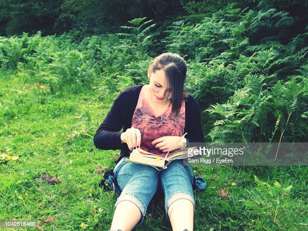 High Angle View Of Young Woman Reading Book While Sitting On Field