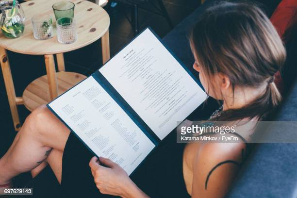high angle view of young woman reading menu while sitting on sofa at cafe - menu stock pictures, royalty-free photos & images
