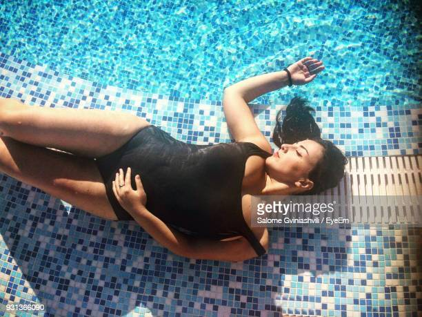 High Angle View Of Young Woman Relaxing At Poolside