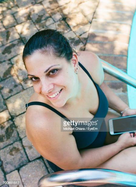High Angle View Of Young Woman Relaxing Poolside