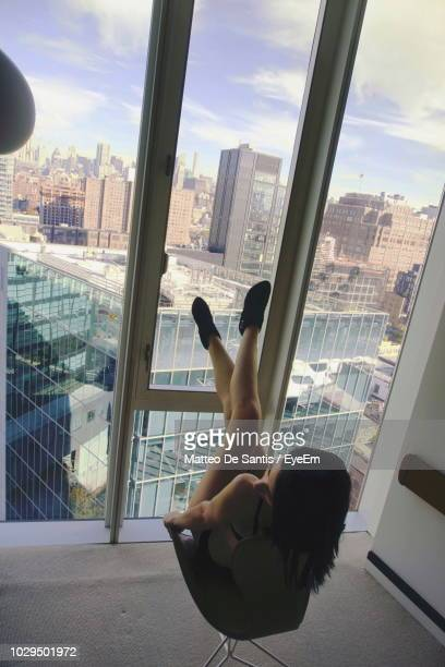 High Angle View Of Young Woman Sitting By Window On Chair At Apartment