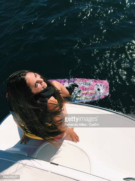 high angle view of young woman sitting on boat - villarrica stock photos and pictures