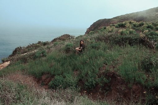 High Angle View Of Young Woman Sitting On Grassy Field By Sea - gettyimageskorea