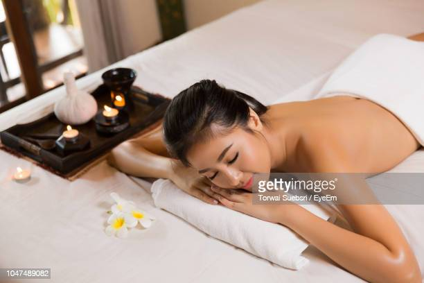 high angle view of young woman sleeping on bed at spa - torwai stock pictures, royalty-free photos & images