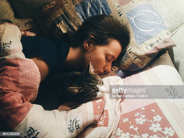 High Angle View Of Young Woman Sleeping With Cat On Bed