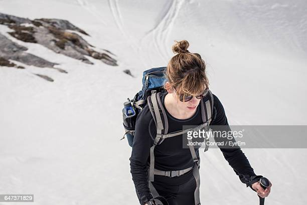 High Angle View Of Young Woman Snowshoeing On Mountain