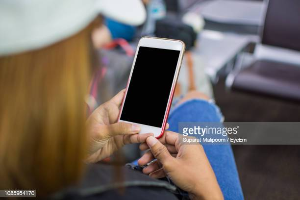 high angle view of young woman using mobile phone while sitting at airport - over the shoulder view stock pictures, royalty-free photos & images