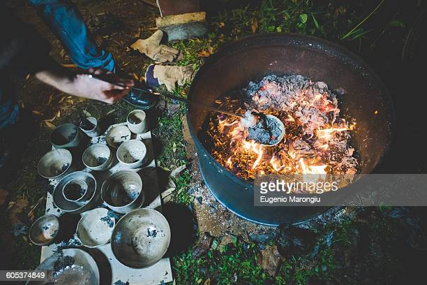 high angle view of young woman using tongs to remove clay pots from fire - one young woman only stock pictures, royalty-free photos & images