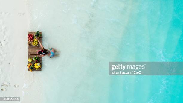 High Angle View Of Young Woman Wearing Bikini With Fruits On Wooden Raft In Sea