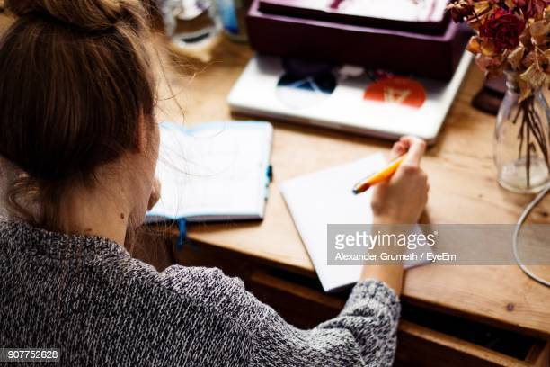 high angle view of young woman working on desk - tagebuch stock-fotos und bilder