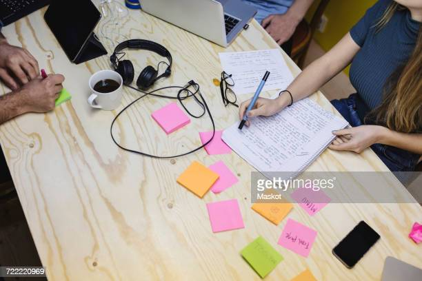 High angle view of young woman writing in book at wooden desk in office