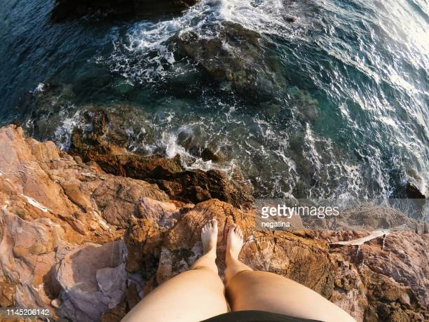 high angle view on the legs of young woman standing on the sea cliff - cliff stock pictures, royalty-free photos & images