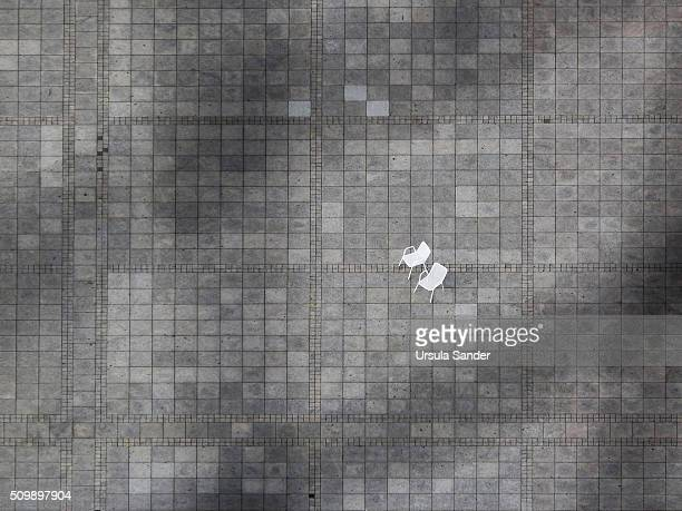 High angle view on two empty white garden chairs on crazy paving
