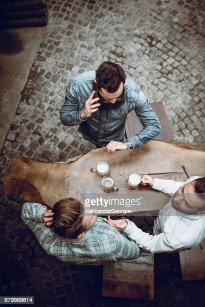 High Angle View Picture of Friends Socializing with Beer in Pub