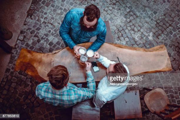 Alto ángulo vista foto de amigos brindando con cerveza en el Pub