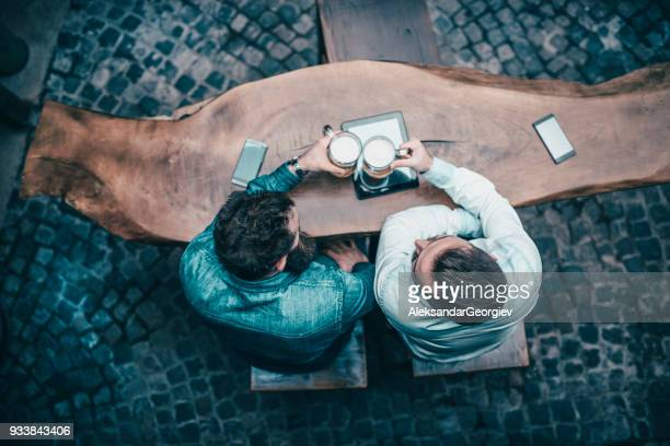 high angle view picture of friends toasting with beer in pub - storyteller stock pictures, royalty-free photos & images