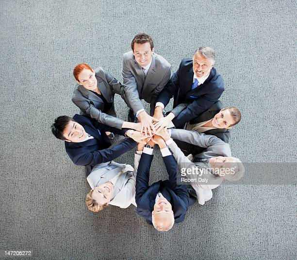 High angle view portrait of business people joining hands in circle